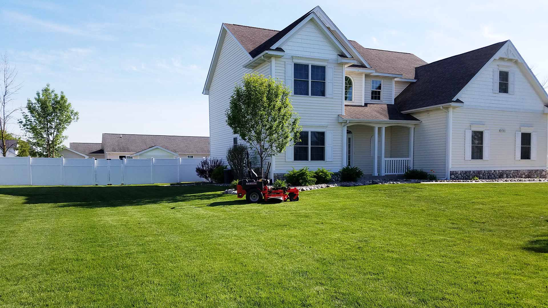 Large, freshly mowed front yard with a parked riding mower.
