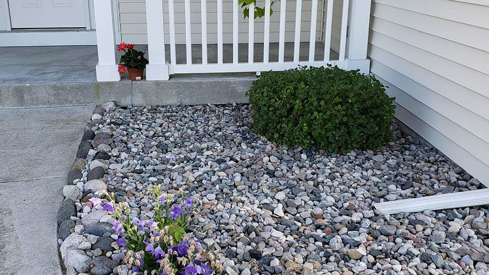 Decorative river rock has been installed in this landscape bed in Bay City, MI.