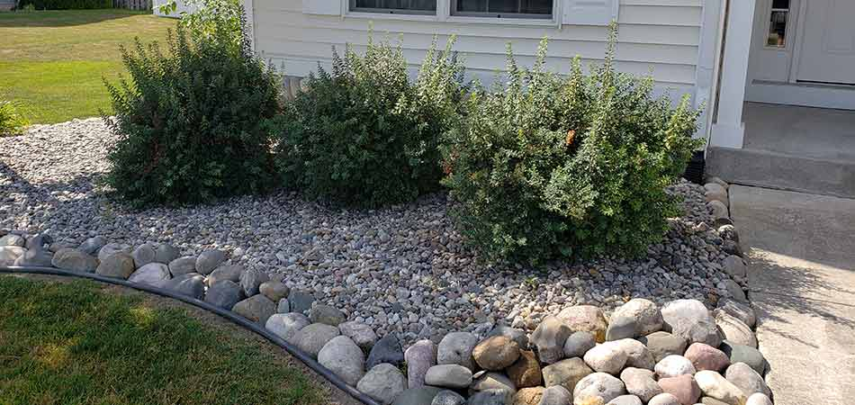 Small river rocks accompanying larger ones in a Midland landscape bed.