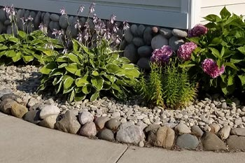 Landscaping bed with river rock and maintained landscaping at a home in Bay City, MI.